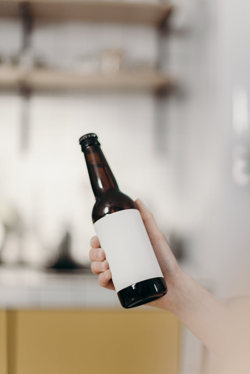 person holding white labeled bottle